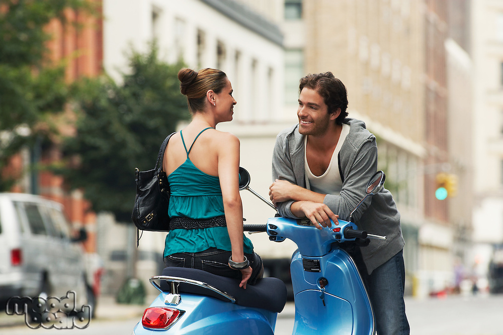 Woman on moped talking to man in street