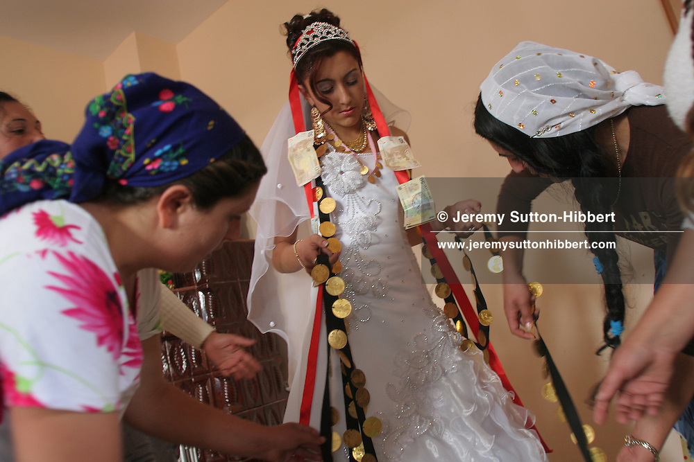 On day two of the wedding celebrations Garoafa Mihai, aged 14, is given her dowry of over 100 gold Franz Josef coins by her family, worth approximately 30,000 USD, prior to her marriage to Florin 'Ciprian' Lulu, aged 13, in Sintesti, Romania, on Sunday, Sept. 24th 2006.  Both are Roma (gypsies) from the village of Sintesti,15 kilometres from Bucharest, Romania. Their partnership was decided by their parents and not through love, and under Romanian law is illegal. The children will neither complete legal paperwork for the wedding, nor visit the local Romanian Orthodox church for a blessing. On her wedding day Garoafa wore approximately 30-40,000 USD of gold Franz Josef coins on her dress, part of the large dowry that she takes with her as she begins her married life. For the guests and for the people of the village another 30,000 USD of pigs, approximately 100,  were killed to be eaten and given away as presents of food. Another 30,000 USD was spent on famous Roma musicians to come and sing 'manele'  type music at the wedding extolling the wealth and status of their patrons for the weekend in their songs.