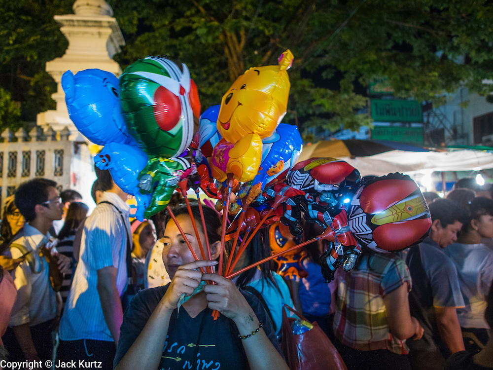 16 NOVEMBER 2013 - BANGKOK, THAILAND: A vendor sells inflatable toys at the Wat Saket temple fair. Wat Saket is on a man-made hill in the historic section of Bangkok. The temple has golden spire that is 260 feet high which was the highest point in Bangkok for more than 100 years. The temple construction began in the 1800s in the reign of King Rama III and was completed in the reign of King Rama IV. The annual temple fair is held on the 12th lunar month, for nine days around the November full moon. During the fair a red cloth (reminiscent of a monk's robe) is placed around the Golden Mount while the temple grounds hosts Thai traditional theatre, food stalls and traditional shows.    PHOTO BY JACK KURTZ