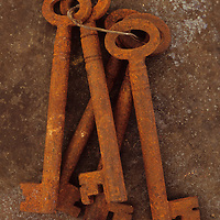 Bunch of rusty old deadlock keys held together by wire lying on tarnished metal