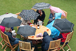 Spectators take shelter under umbrellas as rains halts play during day five of the AEGON International at Devonshire Park, Eastbourne.