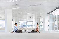 Man and Woman with Laptops in Empty Office Space