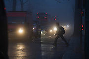 Despite a red light, a schoolboy pedestrian dashes out into commuter traffic at dawn on a foggy morning in south London.