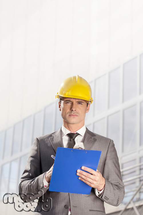 Portrait of confident young male architect writing on clipboard outside building