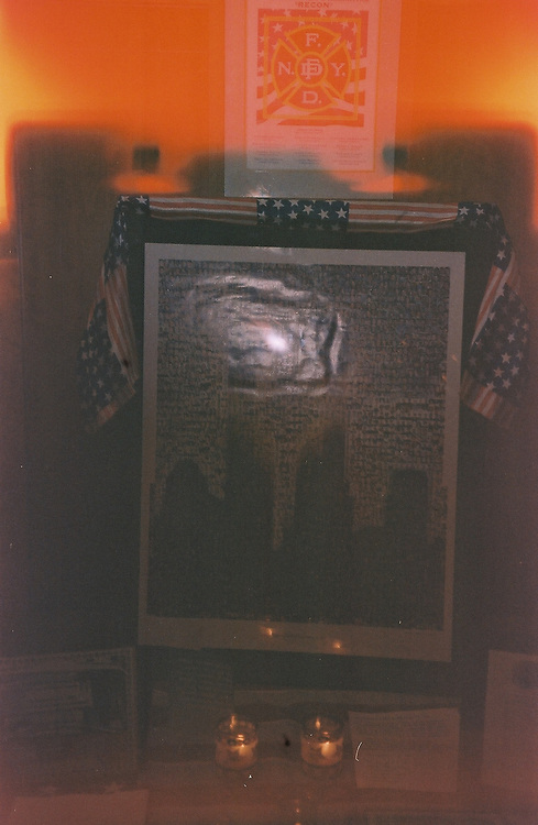 1. When was this photo taken?<br /> <br /> Some time after 9/11<br /> <br /> 2. Where was this photo taken?<br /> <br /> outside a Manhattan firehouse<br /> <br /> 3. Who took this photo?<br /> <br /> I did<br /> <br /> 4. What are we looking at here?<br /> <br /> a flag draped tribute to the fallen firefighters on 9/11, with candles flickering below and a shadow/echo of the FDNY insignia above. The flash of the camera sends an evocative and fraught burst off the framed photo...shocking and harsh.<br /> <br /> 5. How does this old photo make you feel? <br /> <br /> took my breath away; shattered emotions and memories of that day in New York. Loss and sadness, American pride<br /> <br /> 6. Is this what you expected to see?<br /> <br /> No. I barely remember taking the photo, but it must have caught my eye and heart.<br /> <br /> 7. What kind of memories does this photo bring back?<br /> <br /> Beyond the obvious tragedy of 9/11, I acutely remember the thousands of photos draped everywhere to help families and friends find their loved ones. People vanished. In this photo, the tragedy is remembered but not a photo of a person is evident.<br /> <br /> 8. How do you think others will respond to this photo?<br /> <br /> The flash is jarring, and the orange coloring is hot. The color is sort of an echo of the terror. The flag provokes multiple associations. Shattered emotions. Haunting.