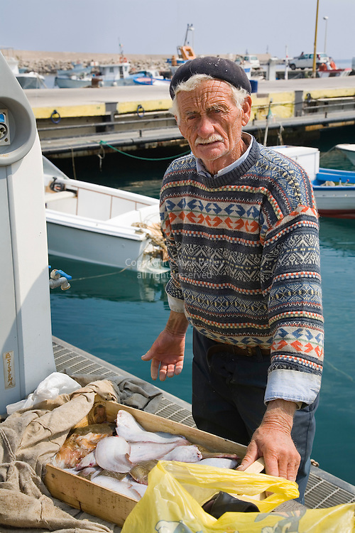 Sicilian fisherman displays his catch of fish at the marina docks, Cefalu, Sicily, Italy