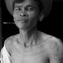 A Cambodian man displays his tattoos.