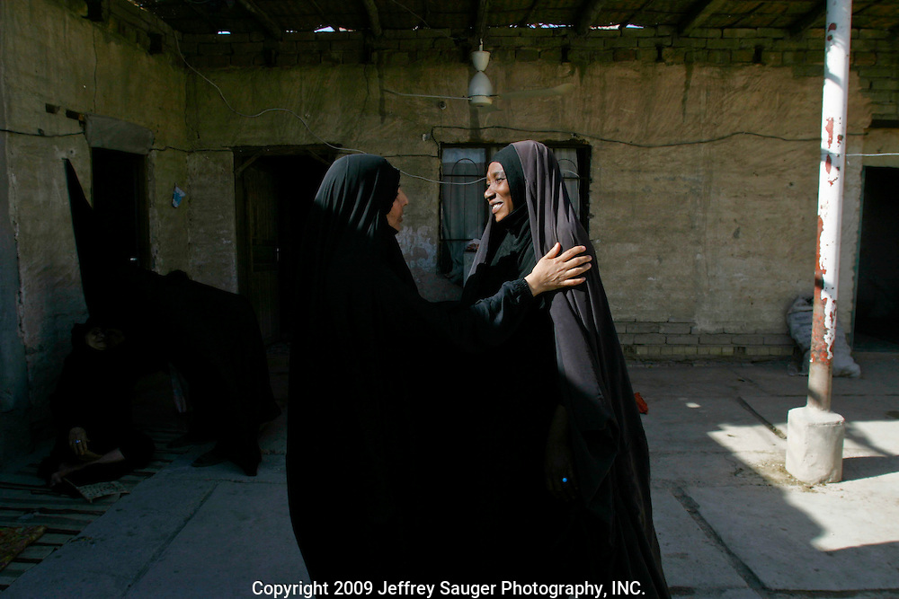 Kawther Al-Kasid, left, greets a friend during the Al-Kasid family's Istikbal, or homecoming, in their home village Suq ash Shuyukh on the outskirts of Nasiriyah, Iraq, July 30, 2003. The celebration lasts three days with different tribal chiefs, family members and friends coming and going. ..The Al-Kasid family fled Iraq after the Gulf War and their part in the uprising against Saddam Hussein in 1991, spent 3 years in Rafa, Saudi Arabia and finally settled in Dearborn, MI. The family hasn't been home to Iraq in 13 years.