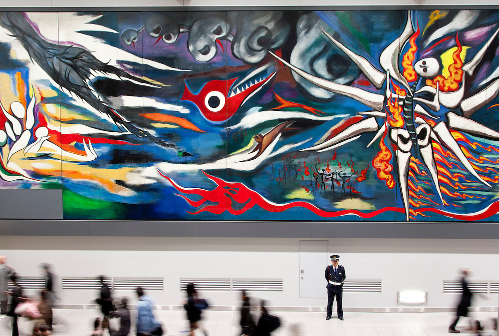 """A security guard stands in front of the 30-metre-long painting called """"Myrth of Tomorrow"""" by the Japanese artist Taro Okamato in Shibuya Station, Tokyo, Japan. Wednesday, November 19th 2008"""
