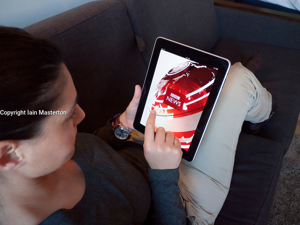 Woman using iPad computer tablet at home to browse BBC news website