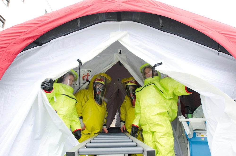 Verpleegkundigen wachten op slachtoffers in de decomtaminatietent. In het Calamiteitenhospitaal in Utrecht wordt een rampenoefening gehouden. De nadruk ligt op de contaminatie, door een gekantelde vrachtwagen zijn veel slachtoffers in aanraking gekomen met een chemische stof. Voor het eerst wordt er geoefend met een zogenaamde decontaminatietent. Als de tent bevalt, schaft het ziekenhuis zo'n tent aan. Bij de 'ramp' zijn 100 slachtoffers gevallen.<br /> <br /> Nurses are waiting at the decontamination tent. In the Trauma and Emergency Hospital in Utrecht an calamity training was held. The emphasis is on the contamination by an overturned truck, many victims are contaminated by a chemical. For the first time a so-called decontamination tent was used. If the tent fulfills the expectations, a tent will be purchased. The 'calamity' caused 100 victims.