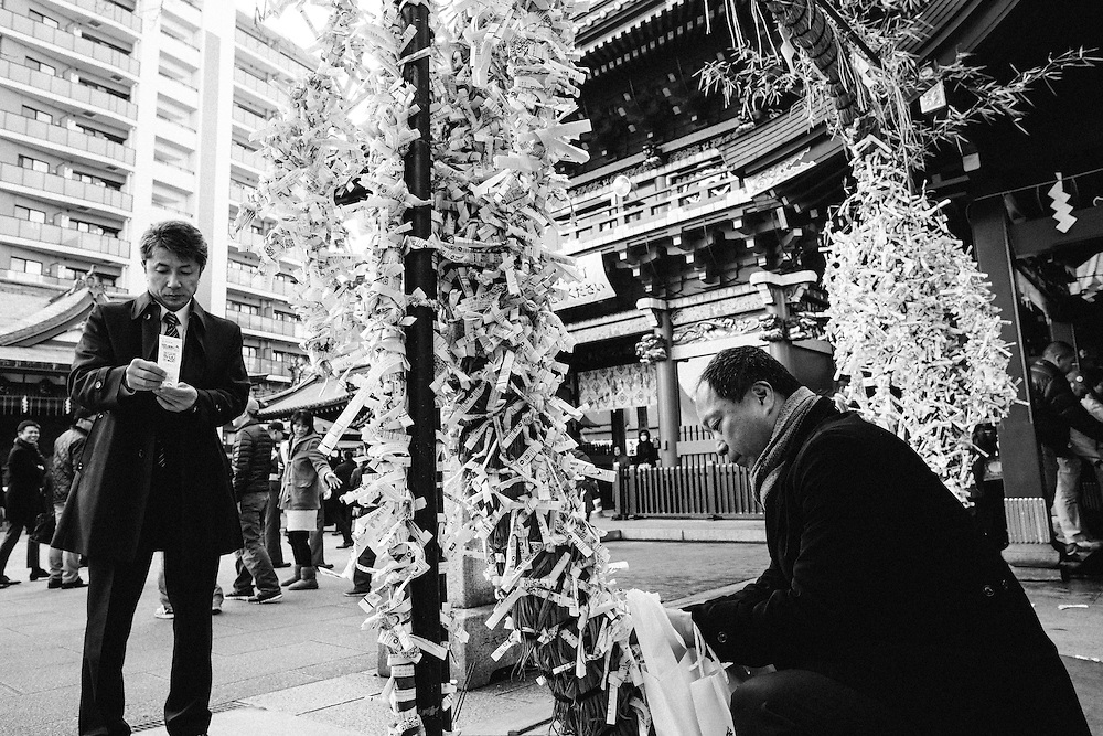 TOKYO, JAPAN - JANUARY 4 : Japanese businessman tying up fortune paper after praying for prosperity of their firms during a New Year's ceremony at Kanda Myojin Shrine in downtown Tokyo, on the first business day of the year Wednesday, January 4, 2017. (Photo by Richard Atrero de Guzman/NURPhoto)
