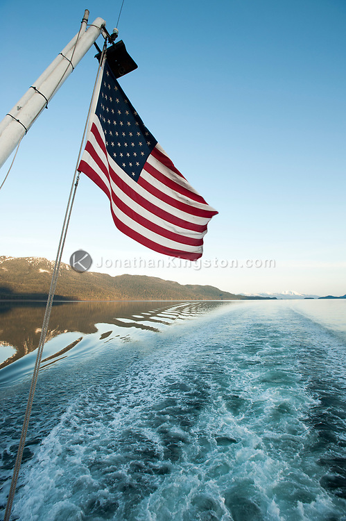 The American flag hangs over the wake left by a small cruise ship.