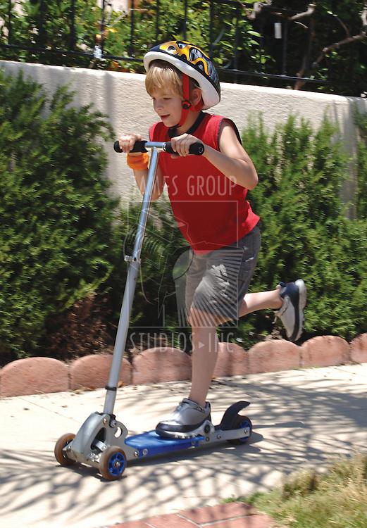 a boy riding a scooter on neighborhood sidewalk