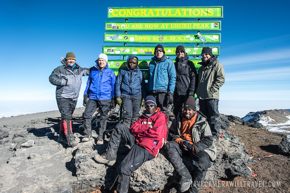 A group of climbers pose for a photo next to the sign marking Uhuru Peak, the highest summit of Mt Kilimanjaro (and highest point in Africa).