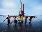 29 JULY 2017 - AIRKUNING, BALI, INDONESIA: Villagers land an outrigger fishing canoe in Airkuning, a Muslim fishing village on the southwest corner of Bali. Villagers said their regular catch of fish has been diminishing for several years, and that are some mornings that they come back to shore with having caught any fish.    PHOTO BY JACK KURTZ