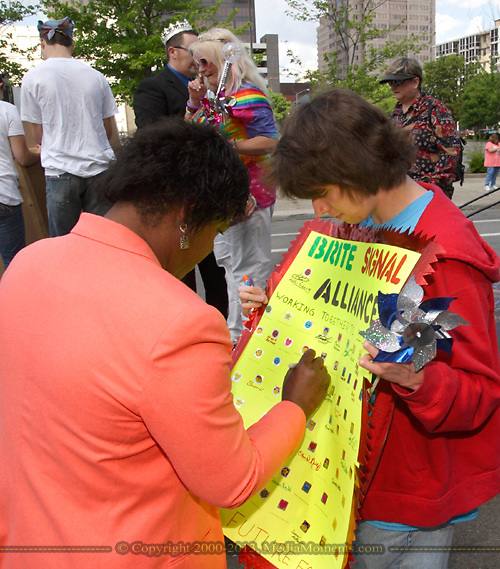 Olivia Freeman adds her name to a sign Steven Powell of Moraine will carry during the annual Dayton Pride Parade and Festival in downtown Dayton, Saturday, June 2, 2012.