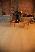 room with 2 chairs and burning wood stove