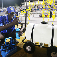 Wuyeh Camara, 15, one of the managers of the Tupelo football team, fills up water bottles on the sidelines of Friday night's game against Oxford.