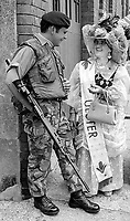 British soldier on duty during The Twelfth parade in Belfast, N Ireland, meets one of the local charactors, Orange Lil, who dresses extravagently for the occasion. 197407120389c<br />