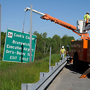 "6/6/11 -- BRUNSWICK, Maine.  Maine department of Transportation workers changed over three signs on highway 295 in Brunswick which used to read ""Brunswick NAS""  to now read ""Executive Airport"" on Monday morning. Photo by Roger S. Duncan."