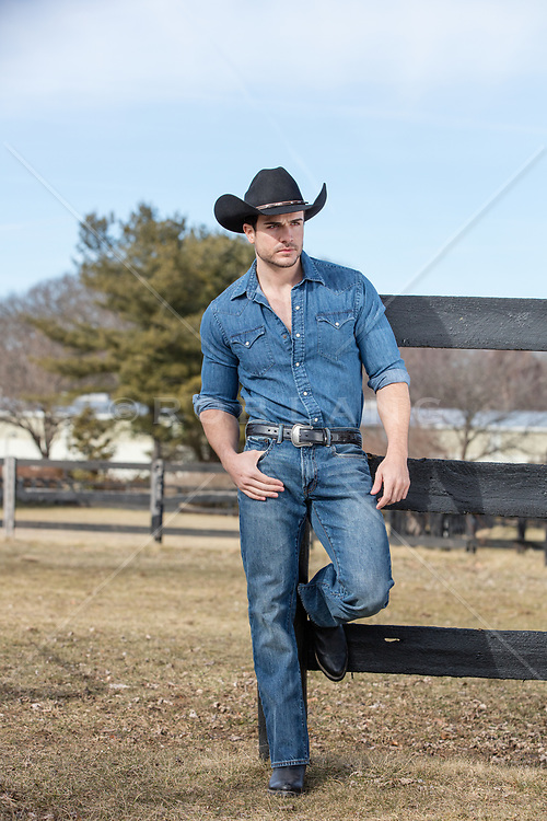 cowboy standing by a fence on a ranch