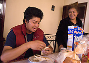 NEWS&GUIDE PHOTO / PRICE CHAMBERS.Cesar enjoys breakfast with his mother Amparo's tamales just as much as she enjoys her son being home. Mexicans often eat a light, late breakfast, a substantial early dinner and a small snack before bed..