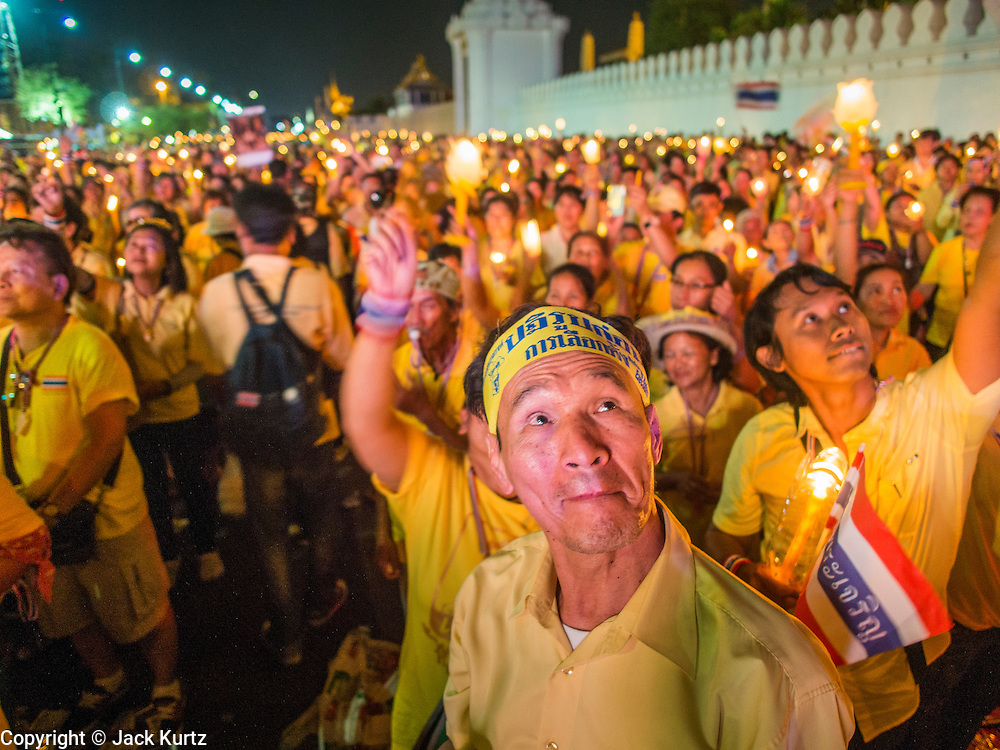 05 MAY 2104 - BANGKOK, THAILAND: A candlelight vigil for Bhumibol Adulyadej, the King of Thailand, in front the Grand Palace in Bangkok. Thousands of Thais packed the area around Sanam Luang and the Grand Palace Monday evening for a special ceremony to mark Coronation Day, which honored the 64th anniversary of the coronation of Bhumibol Adulyadej, the King of Thailand. Many of the people also support the anti-government movement led by Suthep Thaugsuban. Most of the anti-government protesters are conservative supporters of the monarchy.    PHOTO BY JACK KURTZ