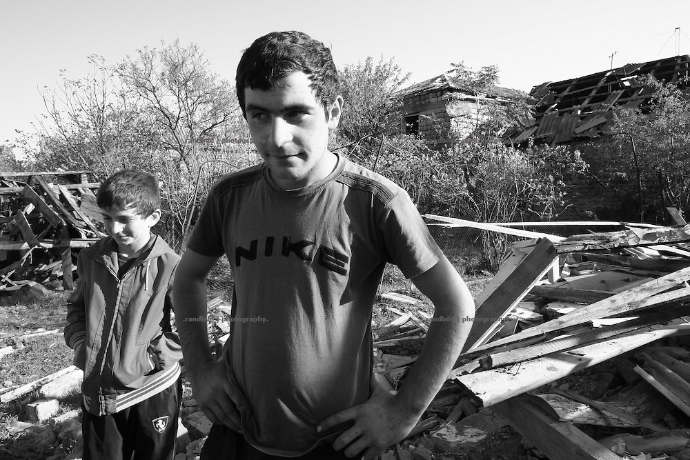 Georgian youngsters standing beside a destroyed house, which was hit by a rocket in Zemo Kikozi, located in the so called bufferzone between Gori and Tskhinvali, few days after the withdrawal of the russian forces from the area. The bufferzone was etablished after a short war in August 2008 as the georgian army assulted South Ossetia to overthrow the local separatist government.