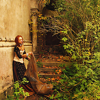 A woman in a vintage costume, standing by the wall of  a historical ruin, and holding a long veil.