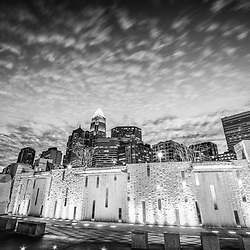 Charlotte skyline at night black and white photo with Romare Bearden Park waterfall fountain and downtown Charlotte buildings against a cloudy sky. Charlotte, North Carolina is a major city in the Eastern United States of America.