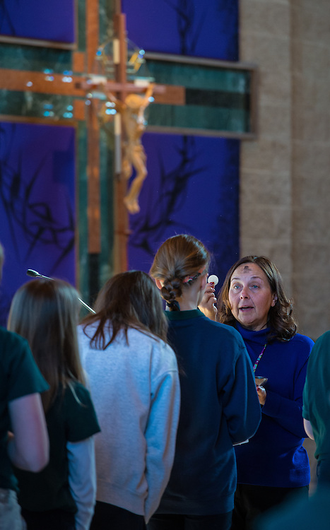 St. Matthew School teacher Teresa Kidder distributes Communion during an all-school Mass on Ash Wednesday. (Sam Lucero photo)