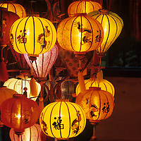 Asia, Vietnam, Hoi An, Shop displays brightly colored silk lanterns along sidewalk at night