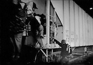 Migrant men climbing up a northbound freight train in the pre-dawn chill of the 2,200 m (6,000ft) high Valley of Mexico, Lecheria train depot, Mexico City, Mexico.  The train will carry them closer to the US border, their destination.