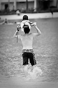 A little girl on a surfboard on top of her fathers head.
