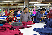 Mohammad, assistant  general manager for Epyllion Group, on the factory floor looking at some of the clothes in production.