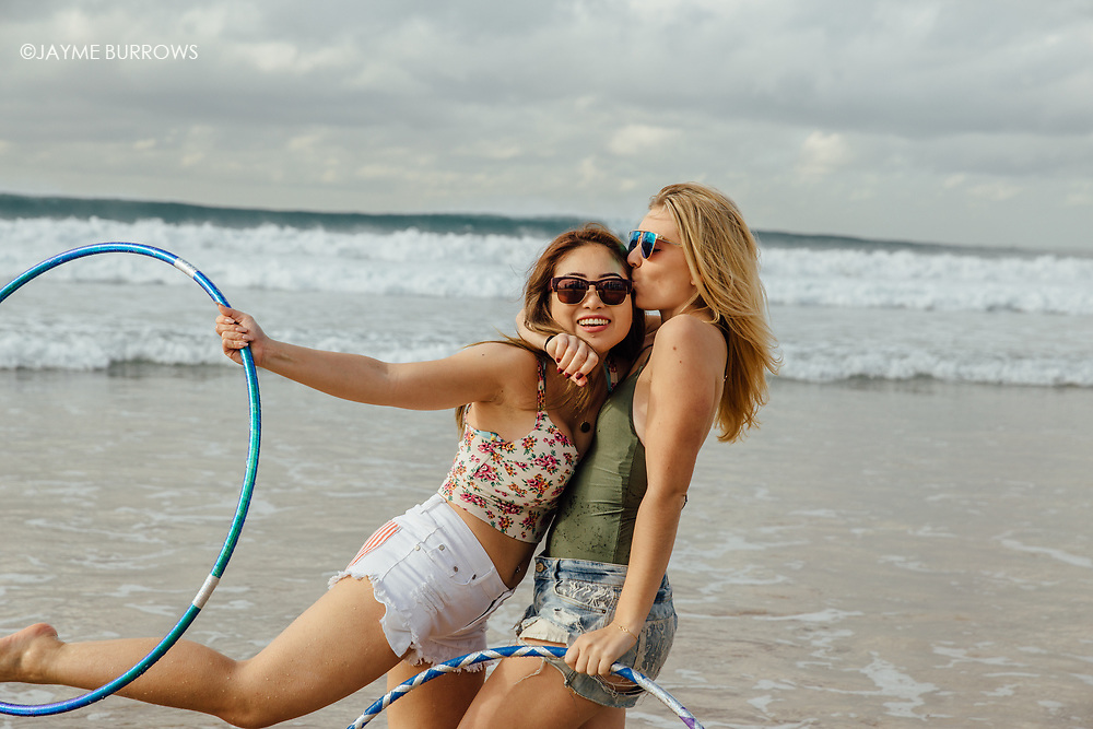 Affectionate blonde plays on the beach with friend.