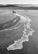 Saline water seeps from a spring onto the Badwater Salt Flat each night and evaporates into a thick salty crust during the heat of the day in Death Valley National Park, California