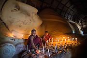 Buddhist monks lighting candles, Bagan, Myanmar
