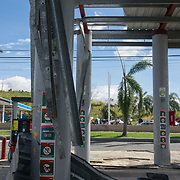 SEPTEMBER 25 - RIO GRANDE, PUERTO RICO - <br /> Damage at a Puma Gas Station as across the street people wait in line at the Gulf Route 66 gas station for a gasoline tanker scheduled to arrive with fuel sometime today. People have been waiting in line inside cars and on foot with gas canisters since before sunrise and the line of cars extended close to one mile.<br /> (Photo by Angel Valentin for NPR)