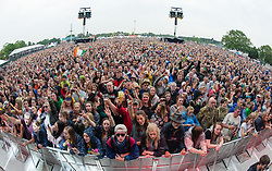© Licensed to London News Pictures. 12/06/2015. Isle of Wight, UK.  Festival goers dance and listen to music in the pouring rain, as Kodaline perform on the main stage at Isle of Wight Festival 2015 on Friday Day 2.  Yesterday the weather was hot and Sunny.  This afternoon has seen torrential rain downpoors.  This years festival include headline artists the Prodigy, Blur and Fleetwood Mac.  Photo credit : Richard Isaac/LNP
