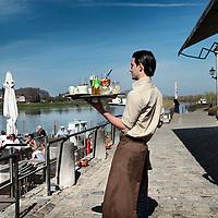 Nederland. Eisden. 10 april 2015.<br /> De eerste echte warme lentedag.<br /> Op het terrasje van eetcafé aon 't Bat genieten de mensen van hun lunch in het zonnetje langs de Maas.<br /> Foto: Jean-Pierre Jans