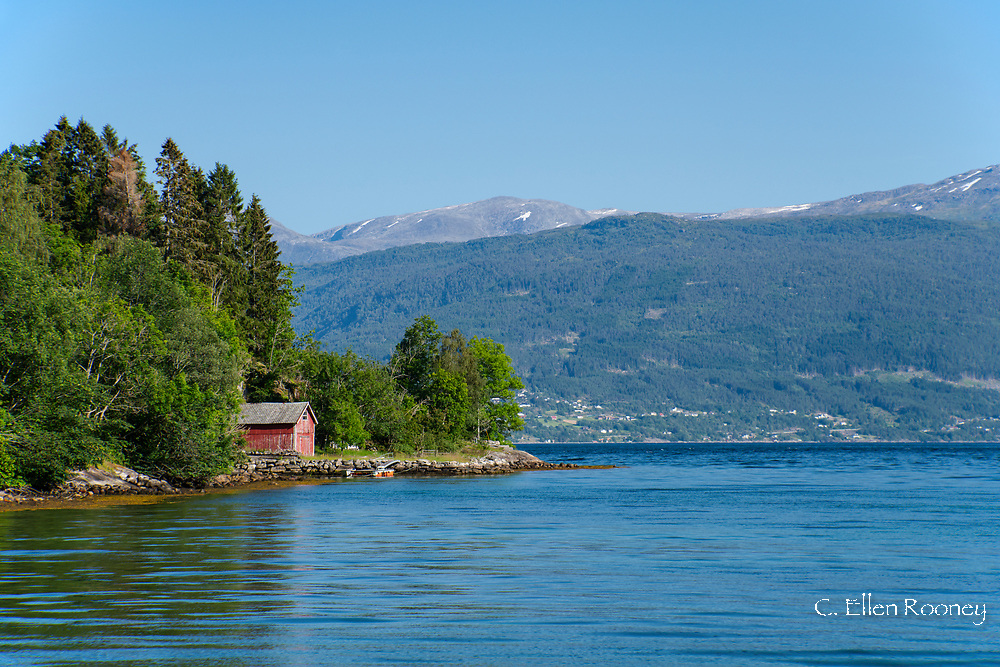 An old red boathouse surrounded by mountains on Ese Fjord, Vestlandet, Norway