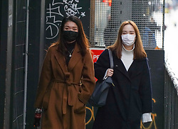 © Licensed to London News Pictures. 31/01/2020. Manchester , UK . Two  women wear a protective mask as they walk  in Central Manchester. Two people in the same family have been diagnosed with the Coronavirus in the UK, which has killed at least 213 people in China Photo credit: Ioannis Alexopoulos /  LNP
