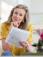 Woman holding paper documents sitting indoors portrait