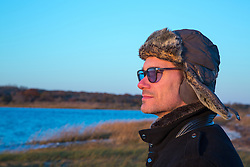 man in a fur hat and glasses looking at the bay in Southampton, NY at sunset