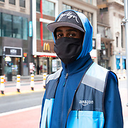 Wearing a face mask, an Amazon delivery person walks in an empty Times Square due to the Coronavirus (Covid-19) outbreak in New York City, New York on Friday, May 8, 2020.  (Alex Menendez via AP)