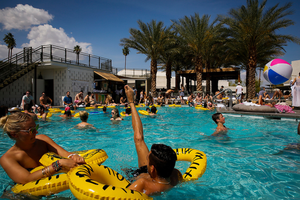 Marianne Lescieux, left, and Nathan Zakhor, center, swim with inner tubes during the Desert Gold 2014 pool party at the ACE Hotel & Swim Club, Coachella weekend on Saturday, April 19, 2014 in Palm Springs, California.© 2014 Patrick T. Fallon, No Use Without Permission