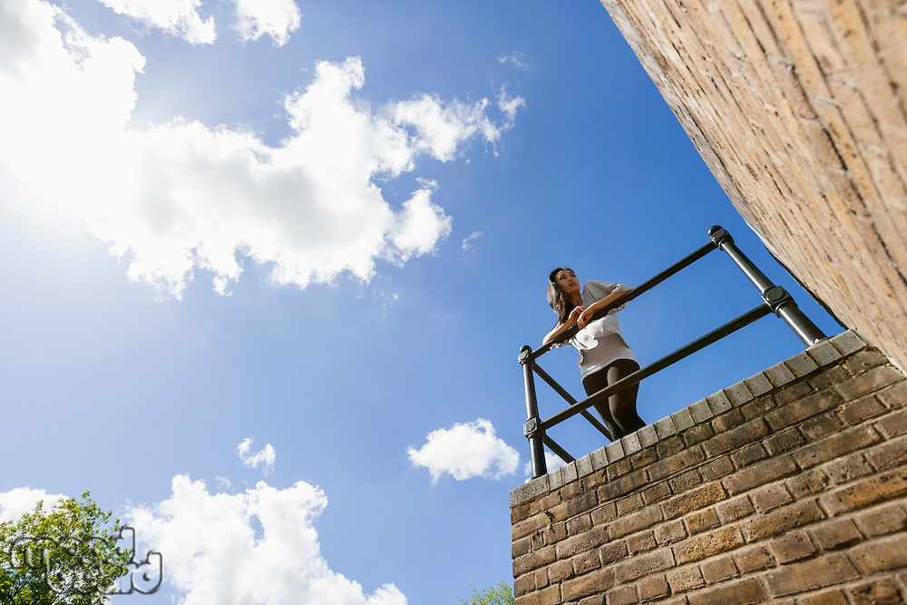 Low angle view of young woman leaning on railing against cloudy sky