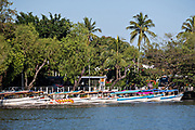 Water taxis called Pangas line up along the shore of Lake Catemaco in Catemaco, Veracruz, Mexico.  The tropical freshwater lake at the center of the Sierra de Los Tuxtlas, is a popular tourist destination and known for free ranging monkeys, the rainforest backdrop and Mexican witches known as Brujos.